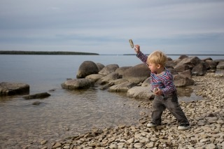 A child throwing a stone into Lake Winnipeg from the shore at Hecla Island