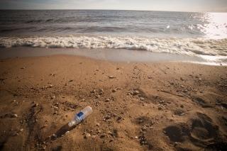 A single-use plastic water bottle in the sand on a Lake Winnipeg beach