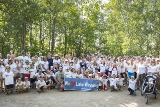 A group photo of all the people and children who participated in the Victoria Beach Walk for Water event in 2017, with the children holding a banner that says we love Lake Winnipeg.