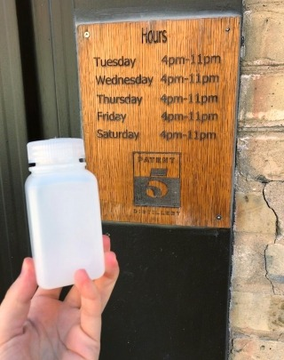 A hand holding a donated bottle in front of the Patent 5 distillery sign