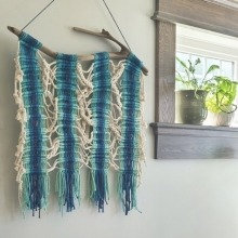 Macrame art hanging on a wall next to a window with two potted plants