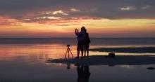 People watching a sunrise on Lake Winnipeg