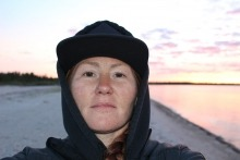 Becky Cook standing on a beach at sunset
