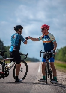 Two cyclists fist-bump as they stand on the highway straddling their bicycles