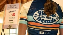 A photo with a cyclist wearing a Bike to the Beach jersey in the foreground and a sign with sponsor logos in the background