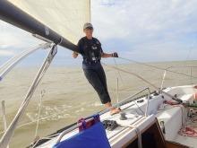 A photo of Karen Scott standing on a sail boat.