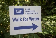 """Lawn sign that says """"walk for water"""" with an arrow giving direction"""
