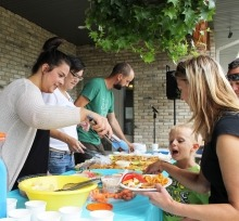 A woman serves fried pickerel to an excited young man and his mom