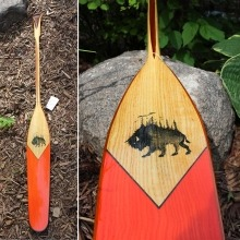 A handcrafted wooden paddle featuring a painting of a bison
