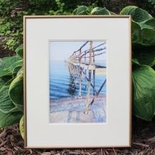 A framed watercolour glicee depicting a Lake Winnipeg pier